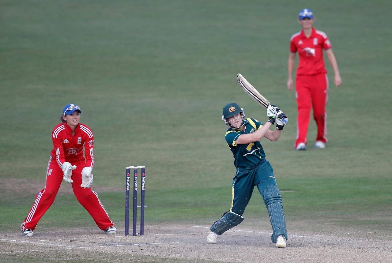 HOVE, ENGLAND - AUGUST 25: Ellyse Perry of Australia hits out as England wicketkeeper Sarah Taylor looks on during the third NatWest One Day International match between England and Australia at the BrightonandHoveJobs.com County Ground on August 25, 2013 in Hove, England.  (Photo by Harry Engels/Getty Images)