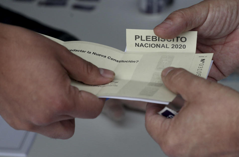 An electoral official delivers a ballot to a voter at a polling station during a referendum to decide whether the country should replace its 40-year-old constitution, in Santiago, Chile, Sunday, Oct. 25, 2020. (AP Photo/Esteban Felix)