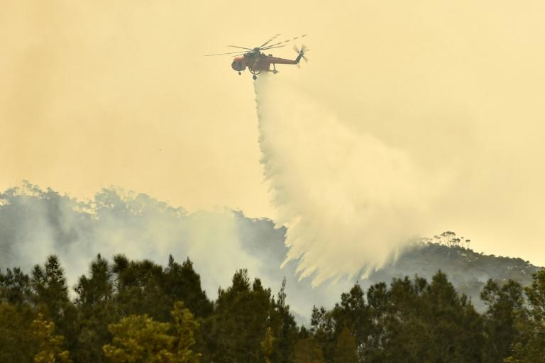 A helicopter drops water on a bushfire near Batemans Bay in New South Wales