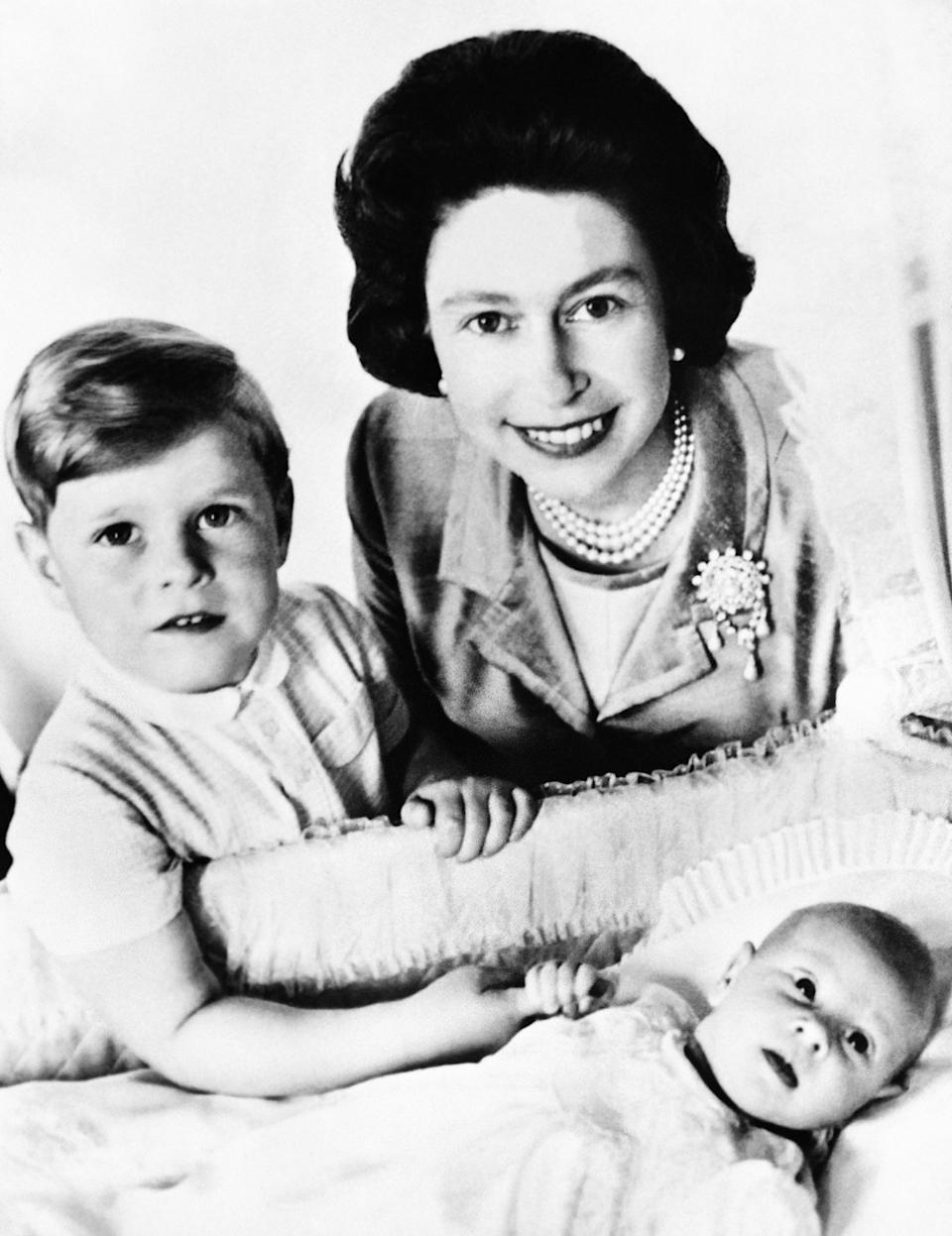 Queen Elizabeth II poses with Prince Andrew and newborn Prince Edward in London in June 1964.