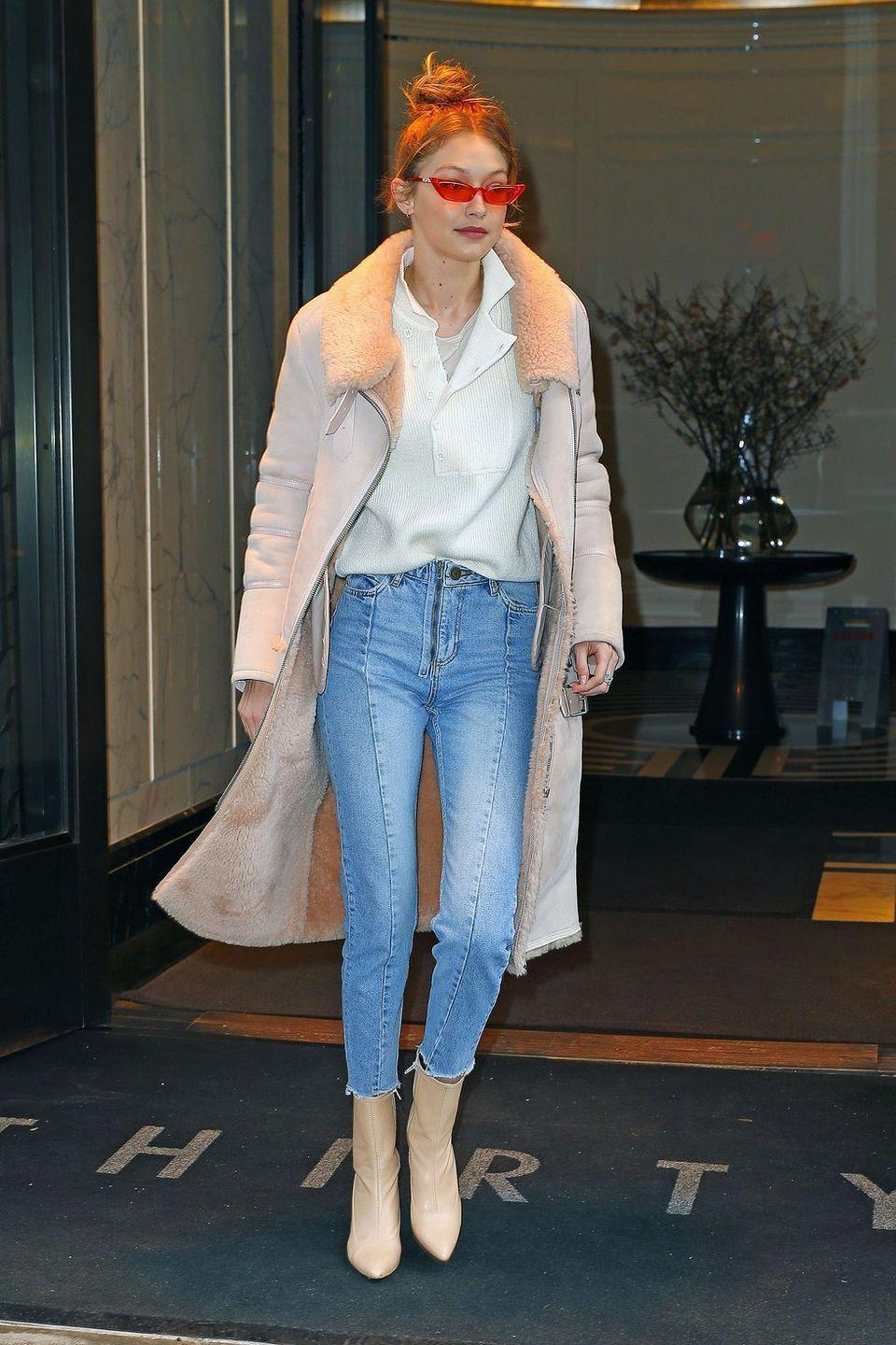 <p>In a fur-lined hushed pink coat by Iro Paris x Kith, white sweater, lightwash Sandro Paris jeans, tan boots, and orange sunglasses while out in NYC.</p>