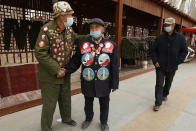 Ethnic minority veterans wearing commemorative buttons, some featuring Chairman Mao Zedong, greet each other at a flea market in Poksam county in northwestern China's Xinjiang Uyghur Autonomous Region on March 21, 2021. Four years after Beijing's brutal crackdown on largely Muslim minorities native to Xinjiang, Chinese authorities are dialing back the region's high-tech police state and stepping up tourism. But even as a sense of normality returns, fear remains, hidden but pervasive. (AP Photo/Ng Han Guan)