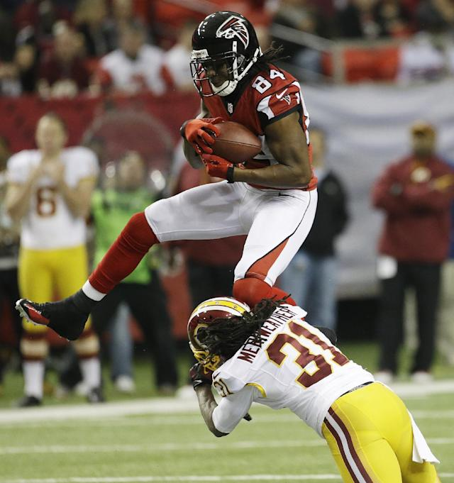 Atlanta Falcons wide receiver Roddy White (84) makes the catch against Washington Redskins strong safety Brandon Meriweather (31) during the first half of an NFL football game, Sunday, Dec. 15, 2013, in Atlanta. (AP Photo/John Bazemore)
