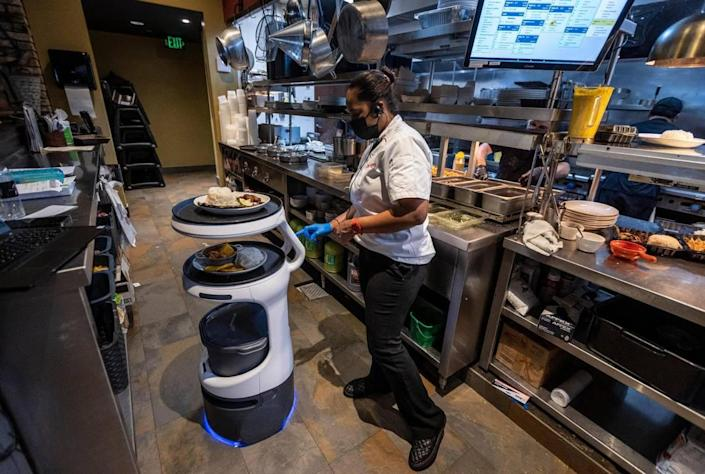 Yei Alayo, a worker in the kitchen at Sergio's restaurant in Kendall, programs a Servi robot server to deliver an order to a specific table inside the dining room, on May 21, 2021. This particular Servi robot was renamed ASTRO.