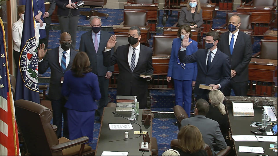 In this image from video, Vice President Kamala Harris swears in Sen. Raphael Warnock, D-Ga., Sen. Alex Padilla, D-Calif., and Sen. Jon Ossoff, D-Ga., on the floor of the Senate Wednesday, Jan. 6, 2021, on Capitol Hill in Washington. (Senate Television via AP)