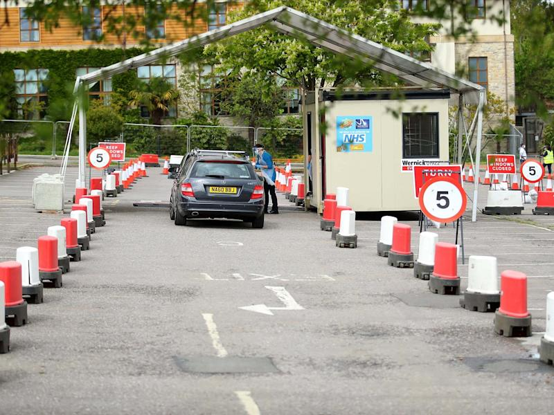 Cars are parked awaiting a swap test at a coronavirus drive-through testing centre in a car park in London: Getty Images