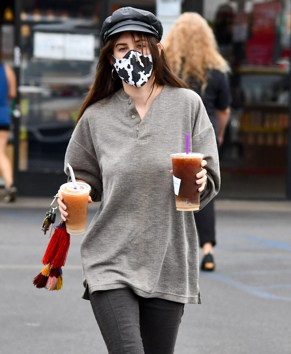 <p>Scout Willis wears a cow-print mask and grabs two drinks to go while out on Thursday in L.A.</p>