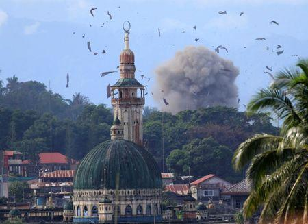 Debris and smoke are seen after an OV-10 Bronco aircraft released a bomb, during an airstrike, as government troops continue their assault against insurgents from the Maute group, who have taken over parts of Marawi city, Philippines.   REUTERS/Romeo Ranoco