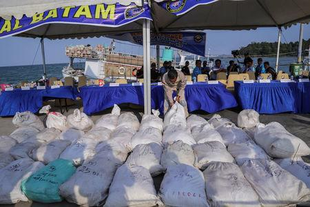 An Indonesian naval officer arranges bags of confiscated crystal meth, part of a 1 tonne seizure, on a dock in Batam, Riau Islands