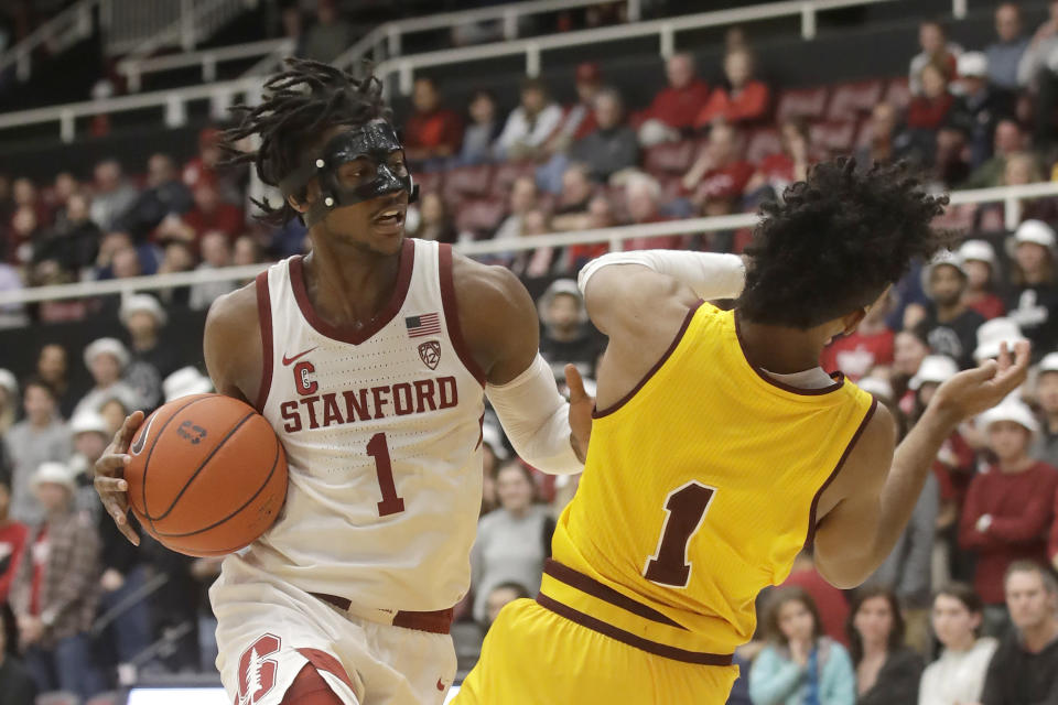 Stanford guard Daejon Davis, left, drives to the basket against Arizona State guard Remy Martin during the first half of an NCAA college basketball game in Stanford, Calif., Thursday, Feb. 13, 2020. (AP Photo/Jeff Chiu)
