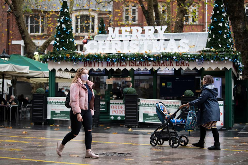 <p>A woman wearing a face mask walks past a cafe with a 'Happy Christmas' sign on The Hayes in Cardiff, Wales</p>Getty Images