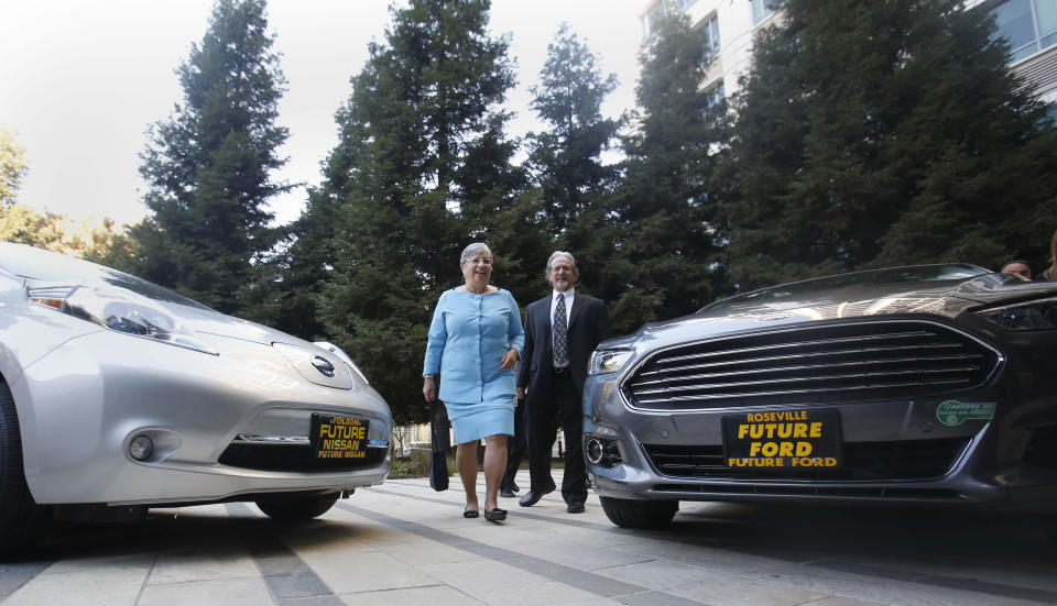 FILE - In this Oct. 24, 2013, file photo, Mary Nichols, chairwoman of the California Air Resources Board, walks between a pair of zero-emission vehicles displayed in Sacramento, Calif. Nichols' term leading CARB ends in December 2020. She's held the role since 2007 after an earlier stint as chair in the early 1980s. Nichols is viewed as a leading contender to be named as Biden's administrator for the Environmental Protection Agency. (AP Photo/Rich Pedroncelli, File)