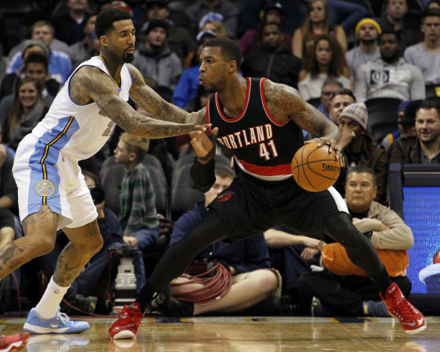 Denver Nuggets forward Wilson Chandler, left, guards Portland Trail Blazers forward Thomas Robinson (41) during the second half of an NBA basketball game Wednesday, Nov. 12, 2014, in Denver. The Trail Blazers won 130-113. (AP Photo/Jack Dempsey)