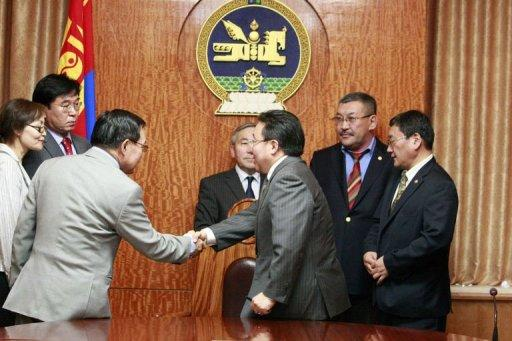 Mongolian President Tsakhia Elbegdorj (C) shakes hands with members of the General Election Committee