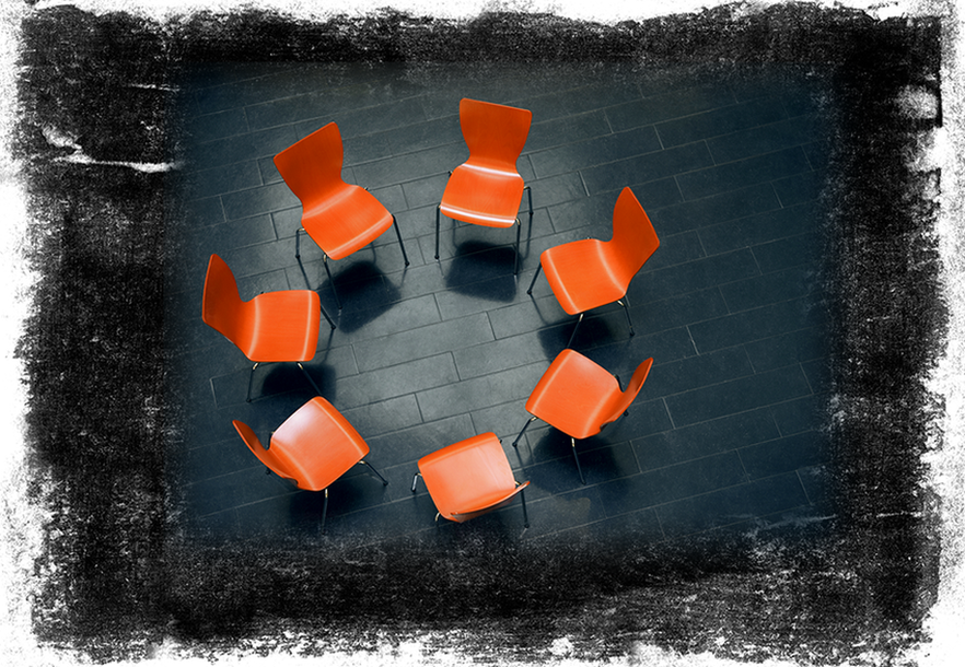 Stock image showing a circle of chairs facing each other on a black rustic background