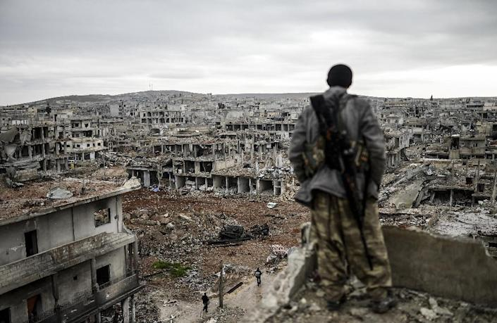 A Kurdish marksman stands on a building overlooking the destroyed Syrian town of Kobane on January 30, 2015 (AFP Photo/BULENT KILIC, -)