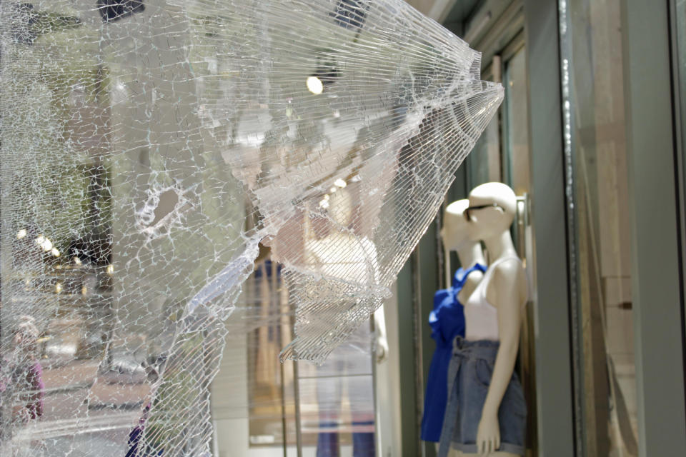 Mannequins are seen through shattered glass at an H&M store in downtown Portland, Ore., Monday, July 13, 2020, after protests the night before. While most demonstrations in the city have been peaceful, nightly violent clashes between police and protesters have divided Portland, paralyzed the downtown and attracted the attention of President Donald Trump, who sent federal law enforcement to the city to quell the unrest. (AP Photo/Gillian Flaccus)