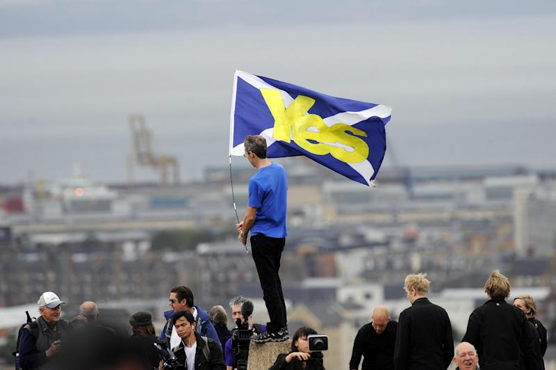 "A pro-independence supporter holds a Saltire flag with ""Yes"" written on it in Edinburgh on September 21, 2013"