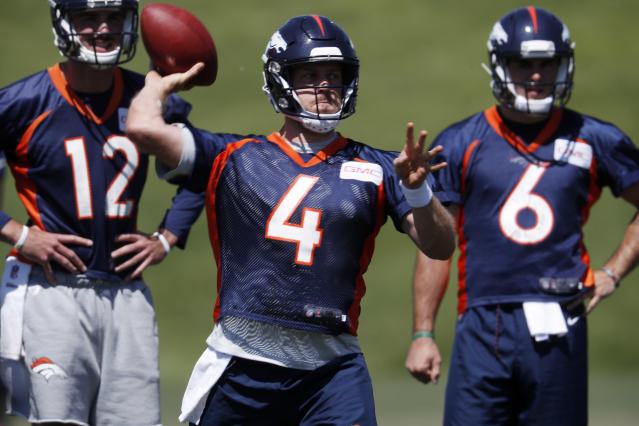 Denver Broncos quarterback Case Keenum, front, throws as quarterbacks Paxton Lynch, back left, and Chad Kelly look on during drills at the NFL football team's training camp, Wednesday, June 13, 2018, in Englewood, Colo. (AP Photo/David Zalubowski)