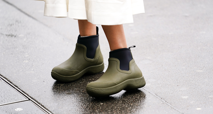 woman wearing white skirt and short green rain boots with black details
