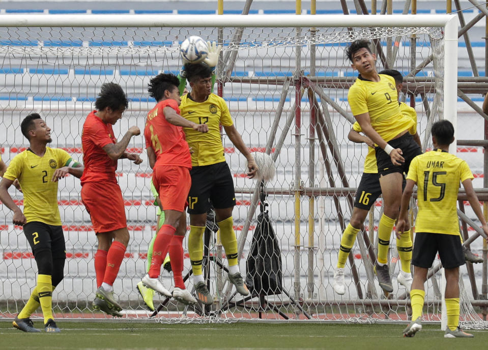 Malaysia's Muhammad Irfan Zakaria, center, defends the goal against Myanmar during their first round Group A football match at the 30th South East Asian Games in Manila, Philippines on Monday, Nov. 25, 2019. The Philippines is hosting the SEA games which officially starts Nov. 30 - Dec. 11. (AP Photo/Aaron Favila)