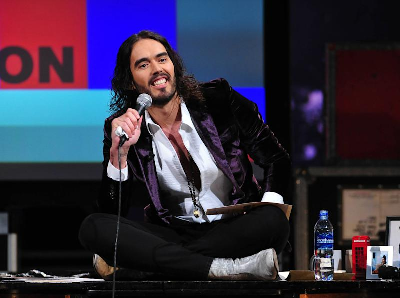"""This March 14, 2013 photo released by FX shows Russell Brand, host of the FX series """"Brand X with Russell Brand."""" The British comedian announced Thursday, June 6, that he's launching a world comedy tour focusing on Che Guevara, Gandhi, Malcolm X and Jesus Christ. Brand says the show examines """"the importance of heroes in this age of atheistic disposability."""" The """"Messiah Complex"""" tour is set to begin August 15 in Abu Dhabi and wrap up Dec. 9 in Iceland. (AP Photo/FX, Ellis O'Brien)"""