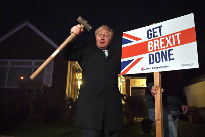 """Britain's Prime Minister and Conservative party leader Boris Johnson poses as he hammers a """"Get Brexit Done"""" sign into the garden of a supporter, in Benfleet, east of London on Wednesday, Dec. 11, 2019, the final day of campaigning for the general election. Britain goes to the polls on Thursday. (Ben Stansall/Pool Photo via AP)"""