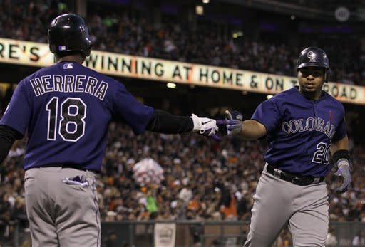 Colorado Rockies' Wilin Rosario (20) is congratulated by Jonathan Herrera (18) after hitting a solo home run off of San Francisco Giants pitcher Ryan Vogelsong during the fourth inning of a baseball game in San Francisco, Monday, May 14, 2012. (AP Photo/Jeff Chiu)