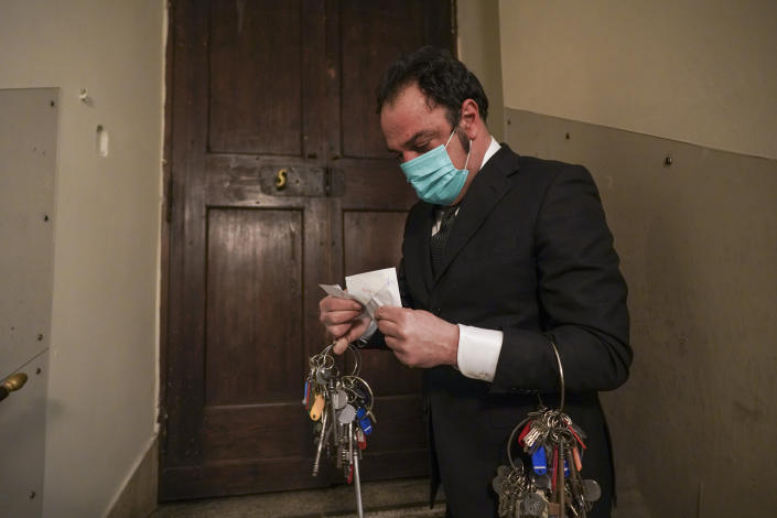 """Gianni Crea, the Vatican Museums chief """"Clavigero"""" key-keeper, opens the sealed envelope containing the 19th century key of the Sistine Chapel, at the Vatican, Monday, Feb. 1, 2021. Crea is the """"clavigero"""" of the Vatican Museums, the chief key-keeper whose job begins each morning at 5 a.m., opening the doors and turning on the lights through 7 kilometers of one of the world's greatest collections of art and antiquities. The Associated Press followed Crea on his rounds the first day the museum reopened to the public, joining him in the underground """"bunker"""" where the 2,797 keys to the Vatican treasures are kept in wall safes overnight. (AP Photo/Andrew Medichini)"""