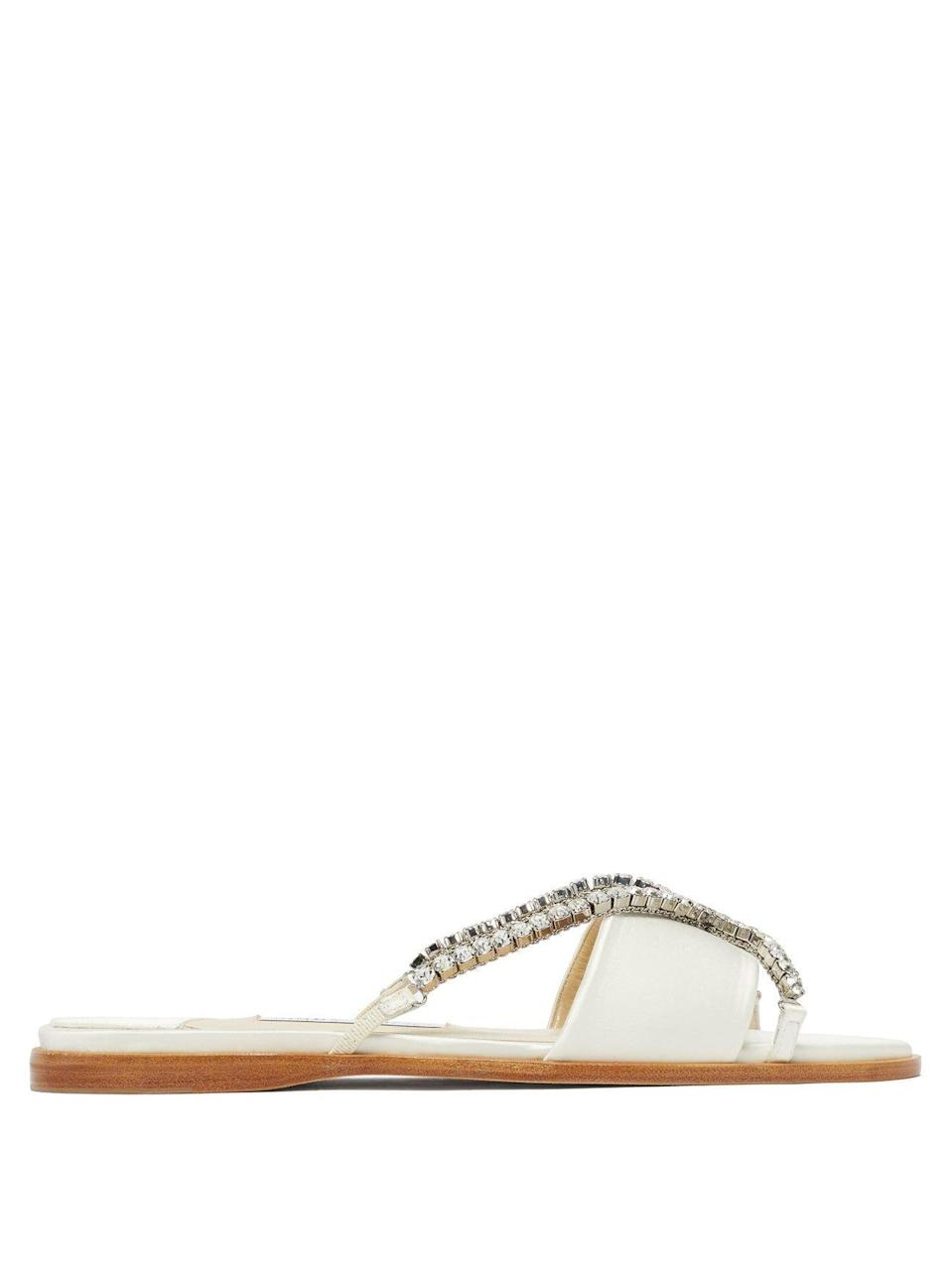 """<p><strong>Jimmy Choo</strong></p><p>matchesfashion.com</p><p><strong>$747.00</strong></p><p><a href=""""https://go.redirectingat.com?id=74968X1596630&url=https%3A%2F%2Fwww.matchesfashion.com%2Fproducts%2FJimmy-Choo-Aadi-crystal-cross-strap-satin-slides-1399047&sref=https%3A%2F%2Fwww.harpersbazaar.com%2Fwedding%2Fbridal-fashion%2Fg36113322%2Fwedding-flats-for-brides%2F"""" rel=""""nofollow noopener"""" target=""""_blank"""" data-ylk=""""slk:SHOP NOW"""" class=""""link rapid-noclick-resp"""">SHOP NOW</a></p><p>Dress up easy slides for the beach—or any summertime wedding dressing—with crystal accents and bridal hues.</p>"""