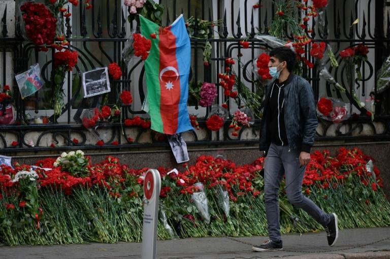 A man walks past a makeshift memorial outside the Azerbaijani embassy in Moscow for Azerbaijanis killed in the conflict over Nagorno-Karabakh