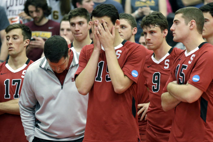 FILE - In this May 3, 2014, file photo, Stanford men's volleyball head coach John Kosty, second from left, looks down as players react after a 3-1 loss to Loyola in the NCAA men's college volleyball championship at Gentile Arena in Chicago. Stanford announced Wednesday, July 8, 2020, that it is dropping 11 sports amid financial difficulties caused by the coronavirus pandemic. The school will discontinue mens and womens fencing, field hockey, lightweight rowing, mens rowing, co-ed and womens sailing, squash, synchronized swimming, mens volleyball and wrestling after the 2020-21 academic year. Stanford also is eliminating 20 support staff positions. (AP Photo/Nam Y. Huh, File)