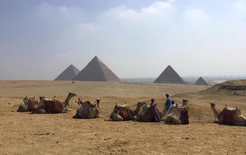 FILE - In this Aug. 30, 2015, file photo, camels rest between rides with their owners against the backdrop of the pyramids in Giza, Egypt. Archaeologists in Egypt say they have discovered a 4,400-year-old tomb near the pyramids outside Cairo. Egypt's Antiquities Ministry announced the discovery Saturday and said the tomb likely belonged to a high-ranking official known as Hetpet during the 5th Dynasty of ancient Egypt. (AP Photo/Courtney Bonnell, File)