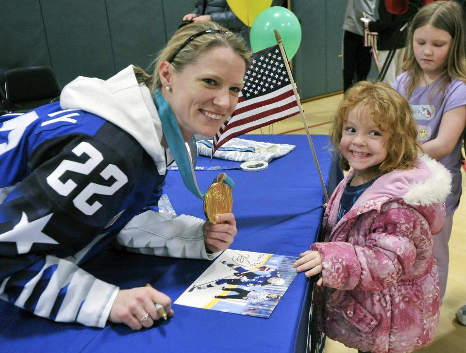FILE - Olympic gold medalist Kacey Bellamy poses for a photo with Addie Raymond, 4, of Westfield, Mass., during a meet and greet reception at the Boys & Girls Club of Greater Westfield, in Bellamy's hometown of Westfield, Mass., in this Saturday, March 10, 2018, file photo. Three-time U.S. Olympian Kacey Bellamy is retiring a month after the women's world hockey championships were postponed. Bellamy, who turned 34 in April, announced her decision Tuesday, May 18, 2021, to retire after 15 years with the U.S. women's national team. (Frederick Gore/The Republican via AP, File)