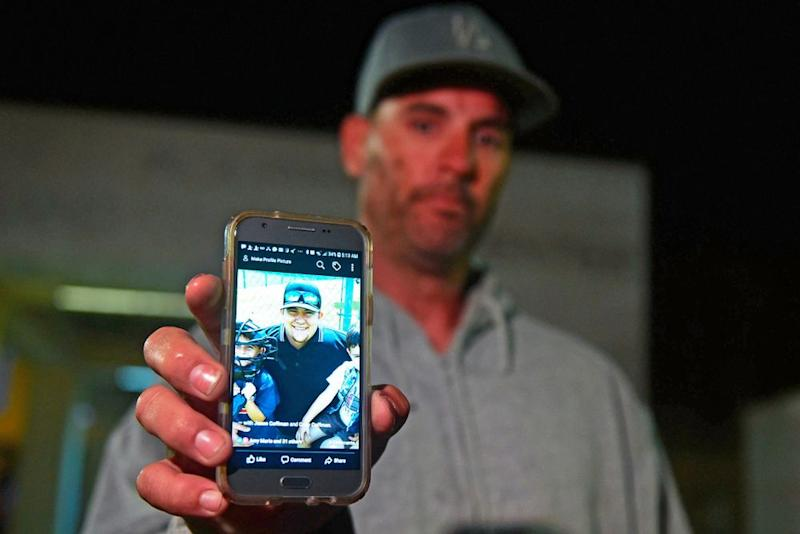 Jason Coffman holds up a photo of his son, Cody