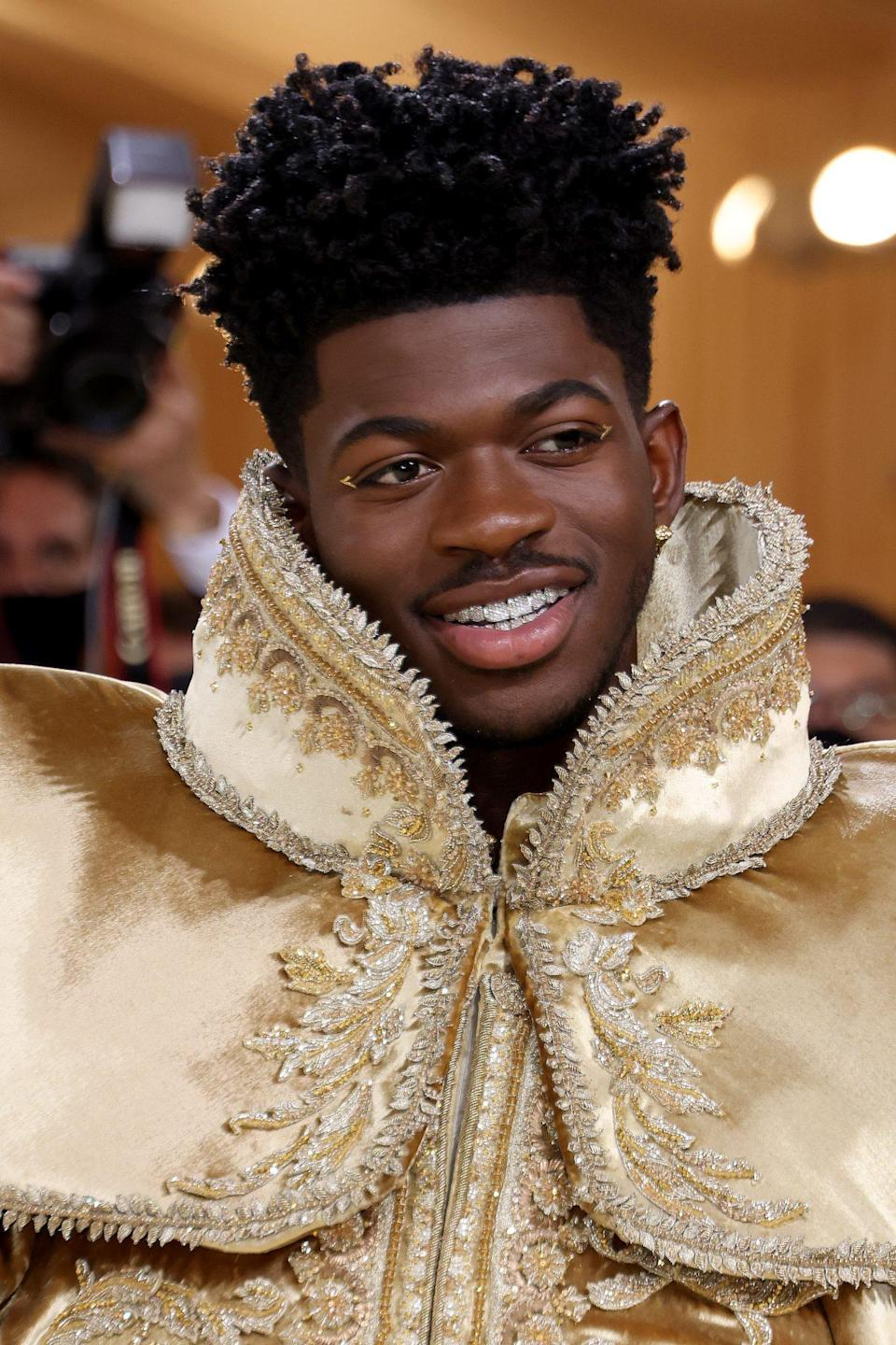 """<p>Gen Z king Lil' Nas X looked stunning on the red carpet. Much like supermodel Iman, the young star's makeup artist <a href=""""https://protect-us.mimecast.com/s/PYTkCkRgRXsnjNOzJSQddaM?domain=autumncommunications-dot-yamm-track.appspot.com"""" rel=""""nofollow noopener"""" target=""""_blank"""" data-ylk=""""slk:Grace Pae"""" class=""""link rapid-noclick-resp"""">Grace Pae</a> added golden decals around his eyes and made sure he had flawless skin by using the <a href=""""https://shareasale.com/r.cfm?b=1649768&u=1772040&m=102659&urllink=https%3A%2F%2Fwww.solawave.co%2Fproduct%2Fsolawave-wand-microcurrent-red-light-therapy-facial-massage-therapeutic-warmth&afftrack=ISWereStillNotOvertheBestBeautyLooksFromthe2021MetGalakgreavesMetGal4544674202109I"""" rel=""""sponsored noopener"""" target=""""_blank"""" data-ylk=""""slk:SolaWave Wand"""" class=""""link rapid-noclick-resp"""">SolaWave Wand</a> along with VERSED's <a href=""""https://protect-us.mimecast.com/s/BuIxCn5l56iG25n5EhpPOoE?domain=target.com"""" rel=""""nofollow noopener"""" target=""""_blank"""" data-ylk=""""slk:DEW POINT Moisturizing Gel-Cream"""" class=""""link rapid-noclick-resp"""">DEW POINT Moisturizing Gel-Cream</a> for skincare, and makeup products from <a href=""""https://protect-us.mimecast.com/s/i3fmCkRgRXsnjNgNEf9rPjo?domain=danessamyricksbeauty.com/"""" rel=""""nofollow noopener"""" target=""""_blank"""" data-ylk=""""slk:Danessa Myricks Beauty"""" class=""""link rapid-noclick-resp"""">Danessa Myricks Beauty</a> before he hit the red carpet. </p>"""