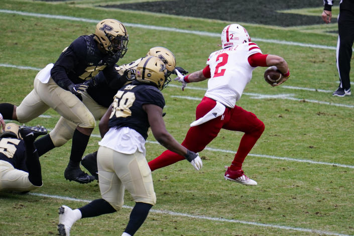 Nebraska quarterback Adrian Martinez (2) breaks away from Purdue defenders on his way to a touchdown during the first quarter of an NCAA college football game in West Lafayette, Ind., Saturday, Dec. 5, 2020. (AP Photo/Michael Conroy)