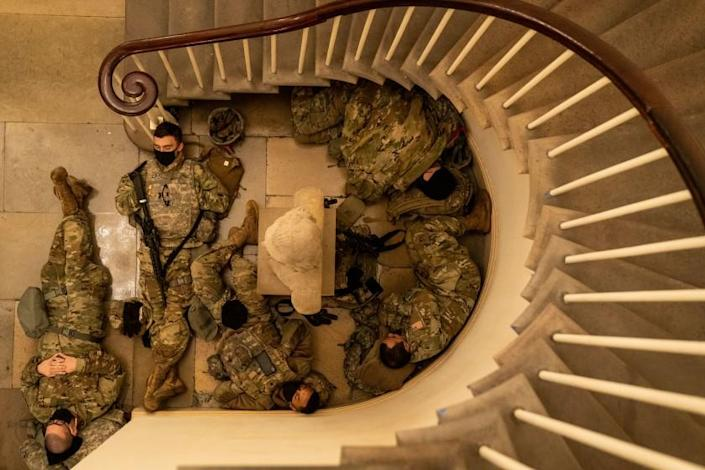 WASHINGTON, DC - JANUARY 13: Members of the National Guard sleep in the halls of Capitol Hill as the House of Representativs convene to impeach President Donald Trump, nearly a week after a pro-Trump insurrectionist mob breached the security of the nation's capitol while Congress voted to certify the 2020 Election Results on Wednesday, Jan. 13, 2021 in Washington, DC. (Kent Nishimura / Los Angeles Times)