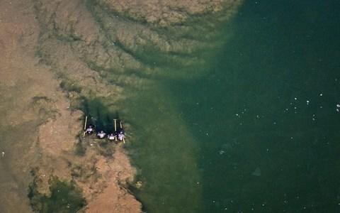 An aerial shot of police officers wading through a pond in search of Libby Squire - Credit: SWNS