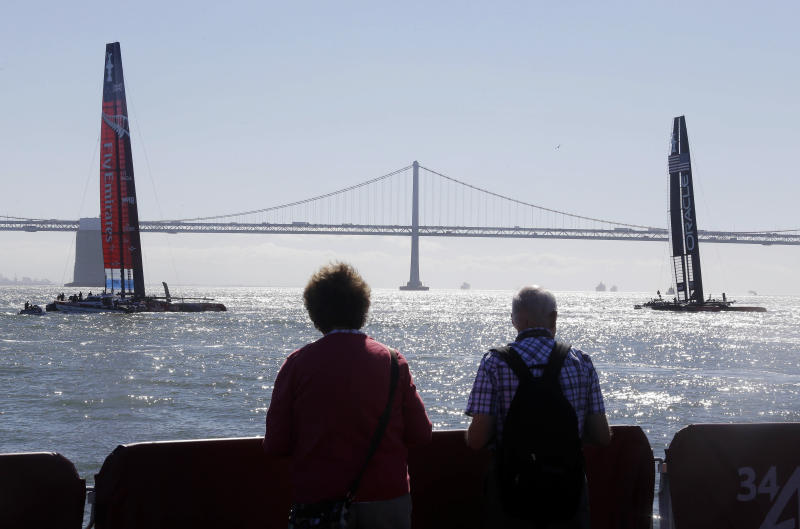 A couple, standing at Pier 27, look out asat Emirates Team New Zealand, left, and Oracle Team USA, right, with the San Francisco-Oakland Bay Bridge in the background, sail before the start of the eleventh and twelfth races of the America's Cup sailing event Tuesday, Sept. 17, 2013, in San Francisco. The races were abandoned Tuesday because of high winds blowing against a strong tide sweeping out of San Francisco Bay. (AP Photo/Eric Risberg)