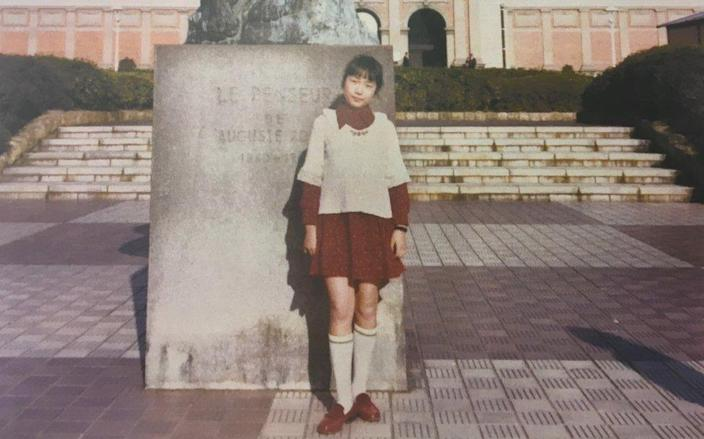 Megumi stands for a picture in a red dress, white jumper and long knee socks