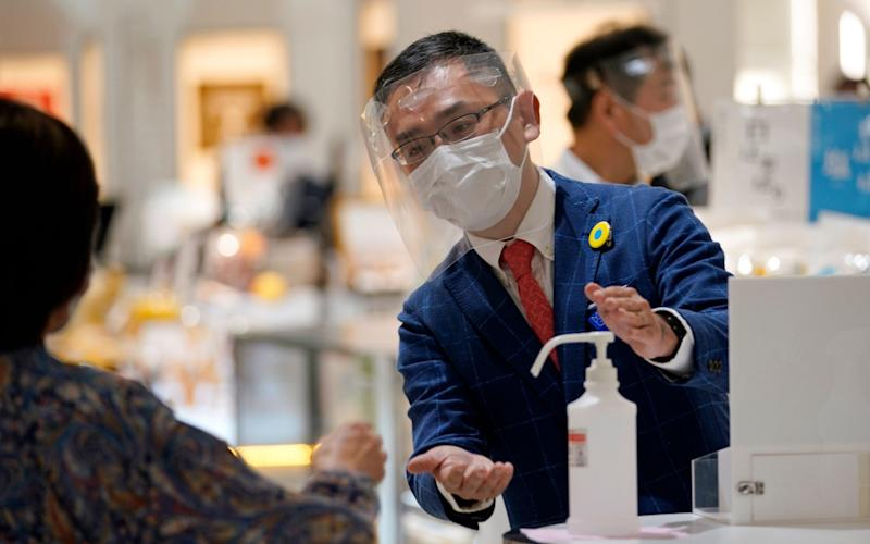 A Matsuya Ginza staff member wearing protective gear invites a customer to use hydroalcoholic solution during the reopening of the department store's food retailing floor after a month and a half of closure - FRANCK ROBICHON/EPA-EFE/Shutterstock/Shutterstock