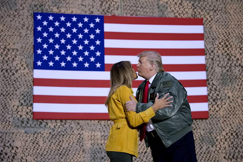 President Donald Trump kisses first lady Melania Trump during a hanger rally at Al Asad Air Base, Iraq, on Dec. 26, 2018. President Donald Trump, who is visiting Iraq, says he has 'no plans at all' to remove US troops from the country.