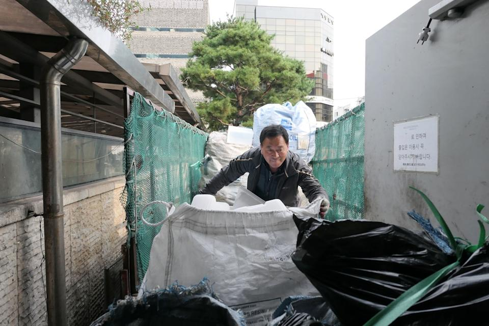 Lee Yong-gi, 62, gathers up bags of recyclables in Seoul.