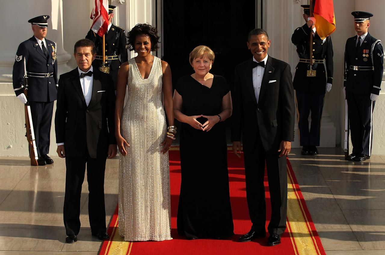 <p>To host German Chancellor Angela Merkel and her husband, Joachim Sauer, for a state dinner in June 2011, Michelle Obama sparkled in a dress completely embellished with gems and stones. (Photo: Getty Images) </p>