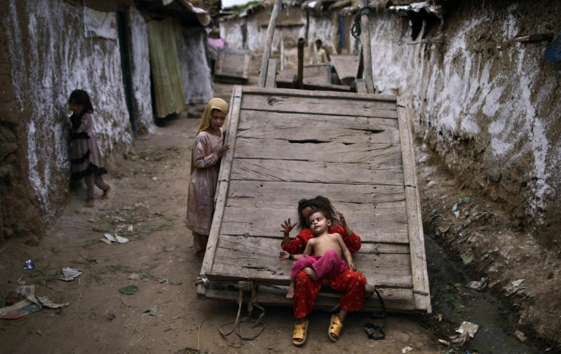 An Afghan refugee girl plays with her sister on a wooden cart parked in an alley of a slum on the outskirts of Islamabad, Pakistan, Thursday, Aug. 16, 2012. (AP Photo/Muhammed Muheisen)
