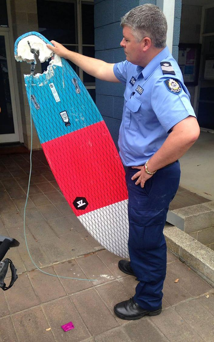 A Policeman displays the surf board with a chunk bitten out of it by a shark that belonged to surfer Laeticia Brouwer, 17, who has been attacked and killed in 2017