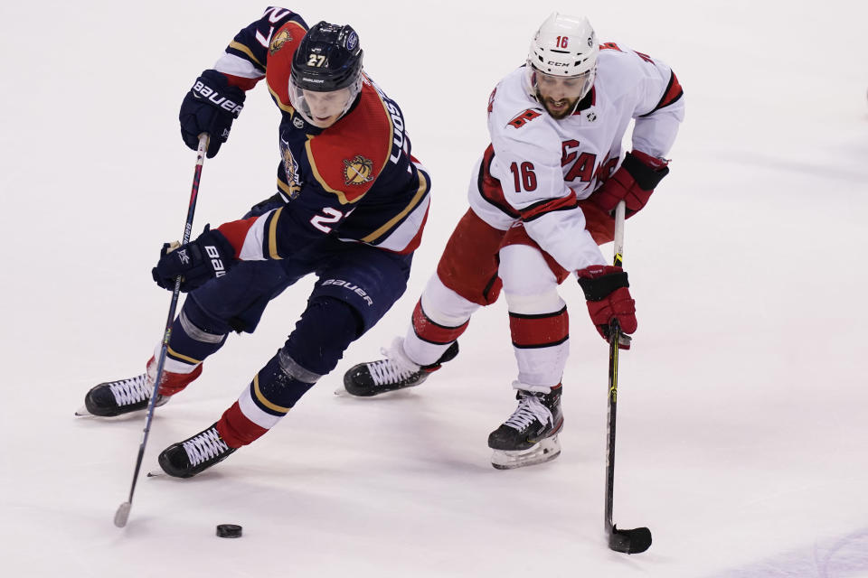 Florida Panthers center Eetu Luostarinen (27) and Carolina Hurricanes center Vincent Trocheck (16) go after the puck during overtime at an NHL hockey game, Saturday, Feb. 27, 2021, in Sunrise, Fla. The Hurricanes defeated the Panthers 4-3. (AP Photo/Marta Lavandier)