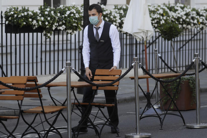 A waiter prepares tables and chairs in an outdoor dining area in London, Thursday, Sept. 24, 2020, after Britain's Prime Minister Boris Johnson announced a range of new restrictions to combat the rise in coronavirus cases in England. (AP Photo/Kirsty Wigglesworth)