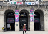 A woman walks past a theater with signs showing it occupied by culture workers, actors students and theater employees in Bayonne, southwestern France, Friday, March 26, 2021. French theaters, cinemas, museums and tourist sites have been closed for much of the past year as part of government virus protection measures, and no reopening plans have been announced. (AP Photo/Bob Edme)